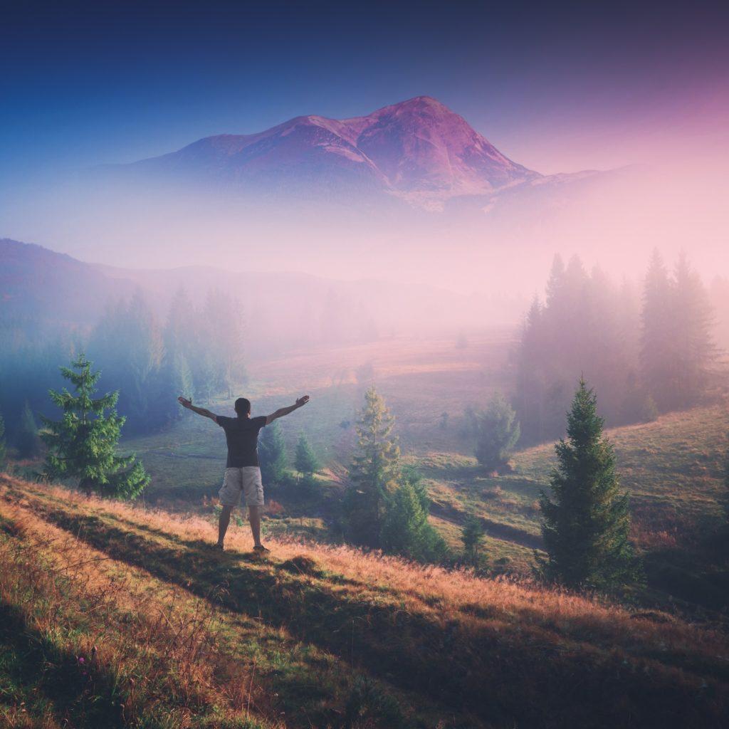 Man on mountain embracing life